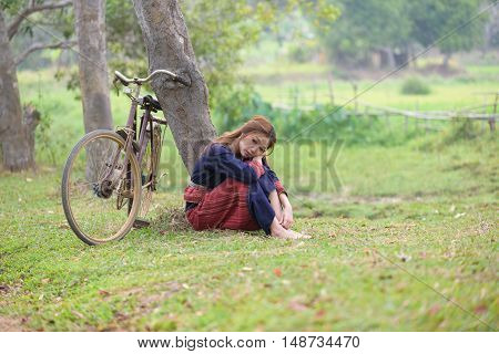 Young asian women inattentive sitting next to tree with bike in rice field area.