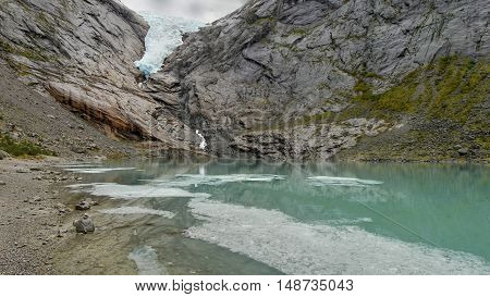 Glacial lake and waterfall under the glacier. Norwegian mountains. poster