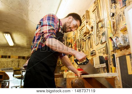 profession, carpentry, woodwork and people concept - happy smiling carpenter working with saw and wood plank at workshop