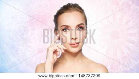 beauty, people and plastic surgery concept - beautiful young woman showing her cheekbone over rose quartz and serenity pattern background