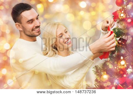family, x-mas, winter holidays and people concept - happy couple decorating christmas tree with ball at home over lights