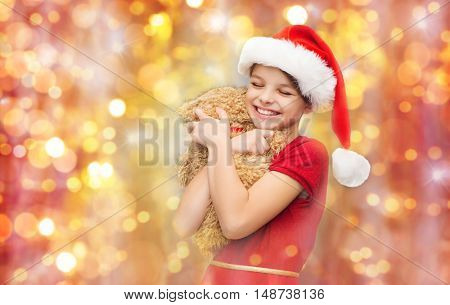 christmas, holidays, children and happiness concept - smiling girl in santa helper hat with teddy bear over lights background