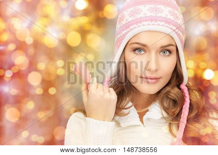 winter, people, christmas and holidays concept - happy smiling woman in hat over lights background