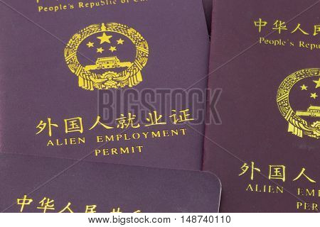 ShanghaiChina 09/25/2016 Several Chinese alien employment permits booklet closeup required for foreigners to work in China