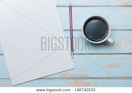 Top view coffee with notepaper and pencil on blue sky wooden floor.