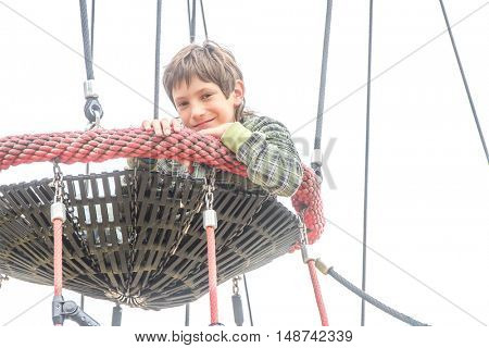 Challenging playground installation with nests and ropes for children to clamber. outdoor child boy portrait enjoying his time on the playground. isolated over white