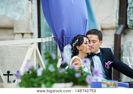 The day of the wedding , the young romantic couple poses for the photographer