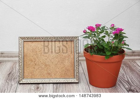 Roses in pot and photo frame on floor