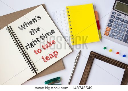 Text When is the right time to take leap on white paper book on table / business concept
