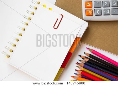 blank paper on desk / Open blank white paper notebook with copyspace and a pen lying on a white desk, view from above / for your text or message / top view