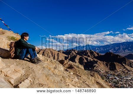 Young Asian Traveler Sitting On High Hills And Looking Away At The Village Over Blue Sky Background