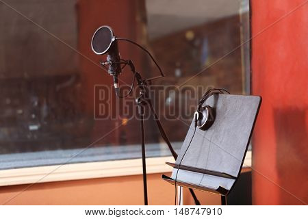 Microphone with headphones in recording studio