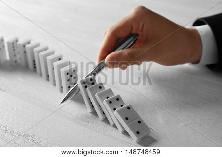 Male hand with pen stopping domino effect on wooden table