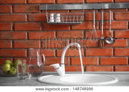 Flowing water into kitchen sink on brick wall background