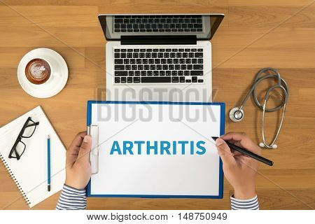 ARTHRITIS Doctor writing medical records on a clipboard medical equipment and desktop on background top view coffee poster