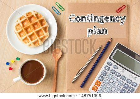 contingency plan text message on paper book and office supplies, pen, coffee on wood desk , copy space / business concept / view from above, top view