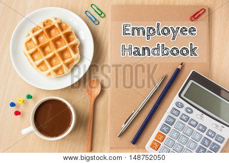 employee handbook text message on paper book and office supplies, pen, coffee on wood desk , copy space / business concept / view from above, top view