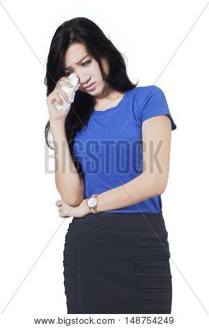 Portrait of a beautiful young woman crying in the studio while holding tissue isolated on white background