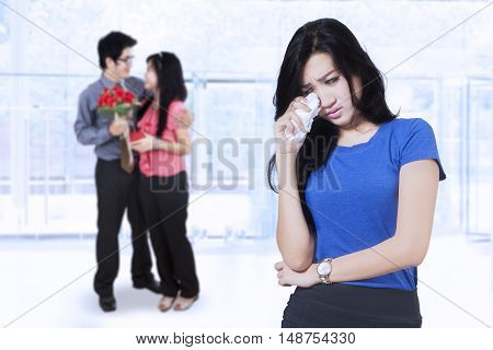 Betrayal concept. Sad woman standing in front of young couple while crying shot in the hotel lobby