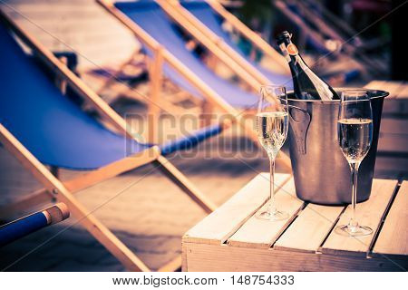 Relaxing with Bottle of Champagne. Beach Chairs and the Glasses of Champagne.