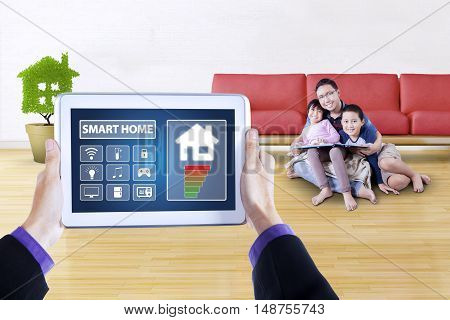 Picture of controller applications of smart home system on the digital tablet screen. Shot with happy father and his children read book on the floor