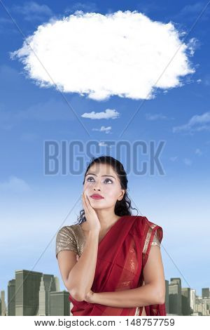 Thoughtful Indian woman wearing saree clothes and looking at cloud speech bubble