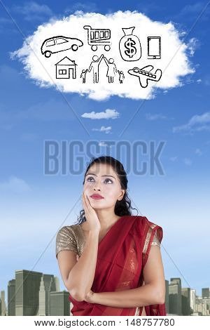 Indian woman wearing saree clothes and imagines her wish on the cloud speech bubble