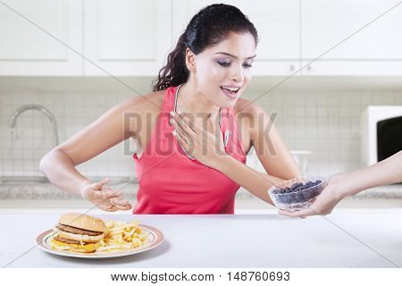 Photo of attractive young Indian woman avoid unhealthy hamburger and choose healthy burger in the kitchen