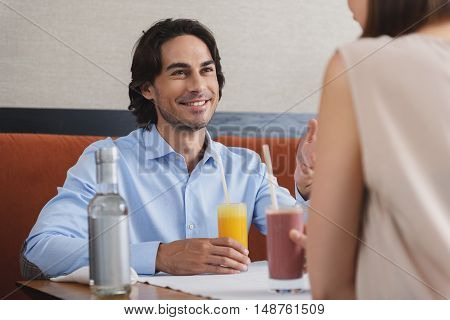 Having great date. Shot of happy smiling couple enjoying lunch together at cafe while drinking fresh juice