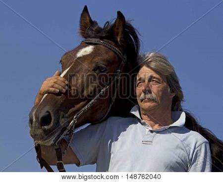 old man stroking his brown horse in nature