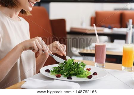 I am having wonderful time. Cropped photo of smiling woman eating salad and sitting at restaurant table during lunch