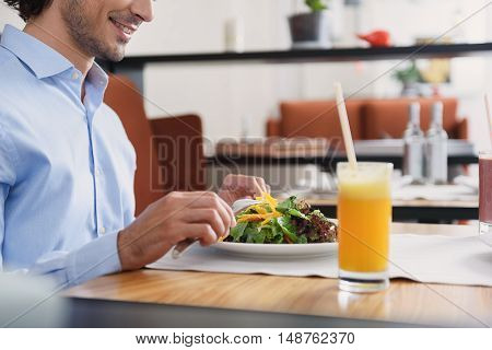 Taking break in cafe. Cropped shot of businessman having lunch in cafe, sitting at table and eating salad, holding cutlery in hands
