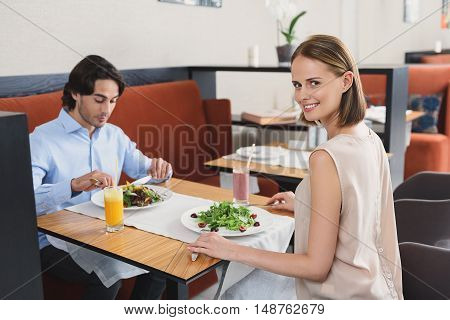 She loves spending time with him. Beautiful woman posing at camera and smiling during lunch with handsome man in background