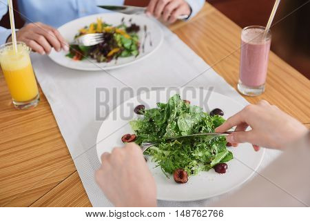 Always have time for healthy food. Close up of woman eating salad in restaurant, holding knife and fork in hands with man sitting in front of her in background