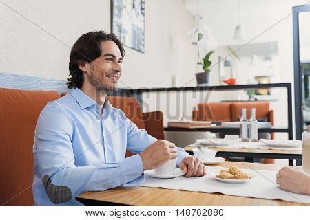 Sharing love of coffee. Attractive young man enjoying cup of coffee in restaurant and looking at his girlfriend, sitting in front of him