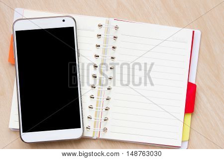 Touch screen smartphone with black screen and Open notebook on desk / open book on wooden table / can be used for your text or artwork / Top view