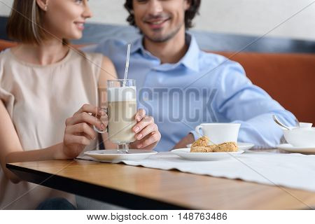 fragrantly and romantically moments. Close up of cup with latte while young couple enjoying date at coffee shop in background