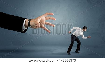 Business man running away from a huge hand concept on background