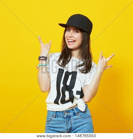 Cool girl in hip-hop clothes making a hand sign and looking at the camera isolated on yellow background. Teenage woman wearing 18 t-shirt and rnb cap