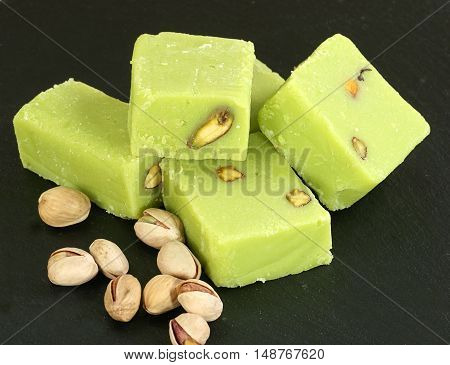 five pieces of pistachio barfi with nuts on a dark slate