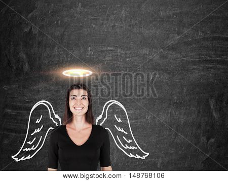 Smiling woman in black dress is standing near blackboard with angel wings and halo above her head. Concept of saint people. Mock up poster