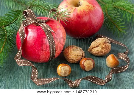 Christmas food background. Apples with nuts on wooden table.