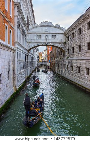 ITALY VENICE - APRIL 2 2016: Gondolier on gondola on the Bridge of Sight taking tourist for a ride. View of the famous Bridge of Sighs in Venice Italy