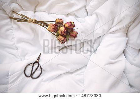Dry Roses And Vintage Scissors On Bed