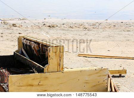 A broken piano carelessly discarded on the shore of the Salton Sea near Bombay Beach in California USA.