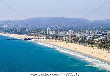 LOS ANGELES, USA - MAY 27, 2015: Aerial view of Santa Monica State Beach in the back residential buildings Santa Monica Pier and the mountains.