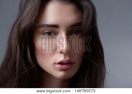 beauty and skincare concept, close up of a serene pretty girl looking into camera