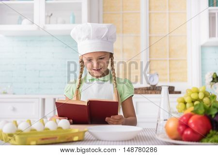 Happy girl is preparing for cooking. She is reading recipe with interest and smiling. She is standing in kitchen at home