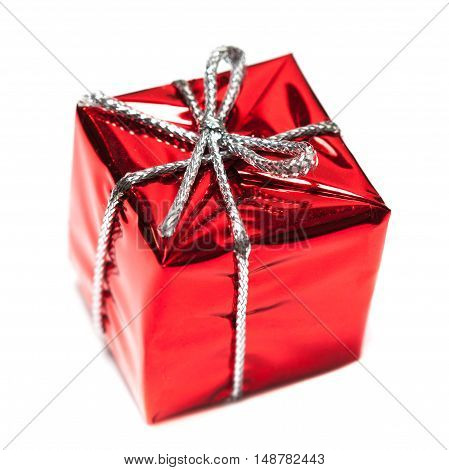 Red gift box with silver ribbon isolated over white close up macro. Christmas red present