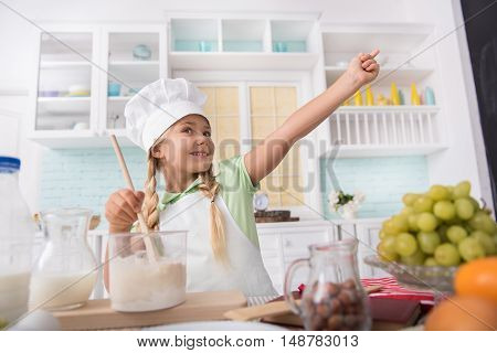Pretty little girl is enjoying baking pasty. She is mixing batter and smiling. Kid is standing and pointing finger sideways